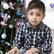 Pensive boy sitting near Christmas tree — Stock Photo #45388765