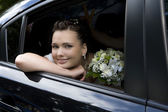 Bride with bouquet sitting in wedding car looking through the wi — Stock Photo