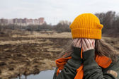 Sad teenager in orange knitten hat and scarf closed her face by hands, stand alone near the scorched field. Spring time — Stock Photo