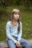 Girl sitting on bench in park — Stock Photo