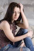 Young attractive serious woman in jeans having hole sitting — Stock Photo