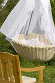 Cradle in the garden. Chair nearby — Stock Photo