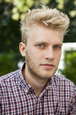 Portrait of blond man with blue eyes in check shirt. one who is aware of the latest trends — Stock Photo