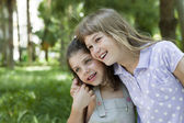 Two sisters hug one another outdoors, happy family — Stock Photo