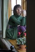 Attractive woman sitting on window-sill — Stock Photo