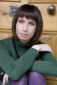 Attractive brunette pensive woman wearing green blouse — Foto Stock