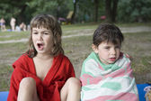 Two little girls sitting on bank of river — Stock Photo