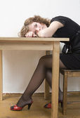 Upset girl in black dress and red shoes put her head down table. — Stock Photo