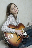 Attractive young woman playing guitar — Stock Photo