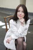 Portrait young woman in white overcoat sitting on chair in stree — Stock Photo