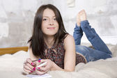 Young attractive brunette woman in jeans lying on sofa — Stock Photo