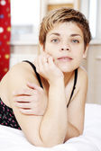 Happy young woman on the bed at home — Stock Photo