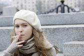 Young teen girl sitting on the jaggies and smoking — Stock Photo