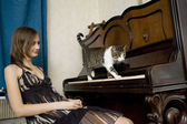 The young woman is watching cat walking on piano — Stock Photo