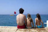 Father with daughters are sitting on piers — Stock Photo