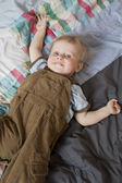 Cute little boy laying in bed — Stock Photo