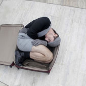 Pensive man in check cap lying in broken trunk — Stock Photo