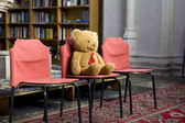 Old teddy bear sitting on chair in local church   in place for children — Stock Photo