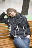 Young attractive teen girl sitting on bench in big Moscow shop after shopping — Стоковое фото