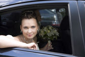 Bride with bouquet sitting in wedding car — Stock Photo