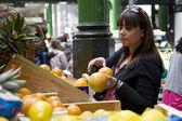 Young woman buying orange at Borough market — Stock Photo