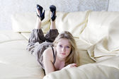 Portrait of sad blond lonely teen girl lying on sofa — Stock Photo