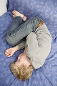 Young blond sad man lying on the bed. — Stock Photo