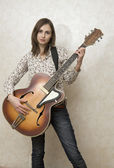 Attractive young woman playing guitar on grey background — Fotografia Stock