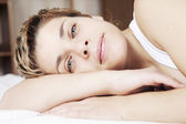 Young blond woman with short hair lying in bed — Stock Photo