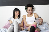 Domestic life: 2 girls choice a comedy movie — Stock Photo