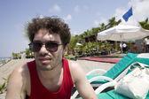 Homem de óculos de sol sentado na praia — Fotografia Stock