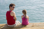 Father and daughter sitting together on piers — Stock Photo