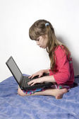 Girl playing with computer — Stockfoto