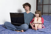 Father and daughter playing game using laptop — Stock Photo