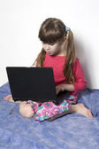Cute little girl playing with laptop  — ストック写真