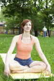 Young woman meditating in a park — Stock Photo
