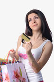The beautiful girl with a credit card and bags — Stock Photo
