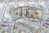 New banknotes on a background of hundred dollars — Stock Photo