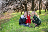 Family walk in the spring garden, mother, father and little daughter — Stock Photo