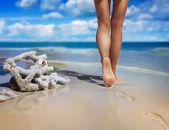 Barefoot female legs on sand — Stock Photo