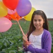 A teenage girl in purple with colorful balloons — Stock Photo #44046291