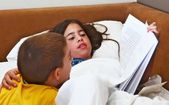 Big sister reading a bedtime book for her little brother - siblings sharing quality time before bed — Stock Photo