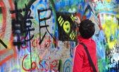 Person adding grafitti to the John Lennon Wall — Stock Photo