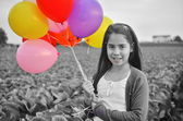 A teenage girl in purple with colorful balloons — Stock Photo
