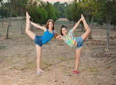 Two best friend girls doing the splits — Stock Photo