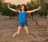 Portrait of a 12 year old girl jumping — Stock Photo