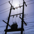 Silhouette of am electrical or utility pole transformer with sun flare — Stock Photo #51476083