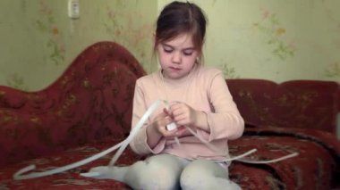 Girl makes the friendship bracelet. She is attentived, focused and serious — Wideo stockowe