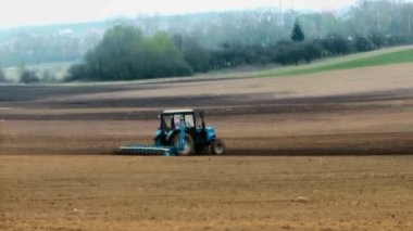 Traktor plows the land in spring — Stock Video