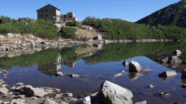 Hombre entrar en la choza en el borde del lago de la montaña — Vídeo de Stock